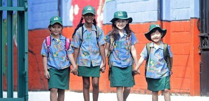 Four students from different background nationalities walking together entering a school.
