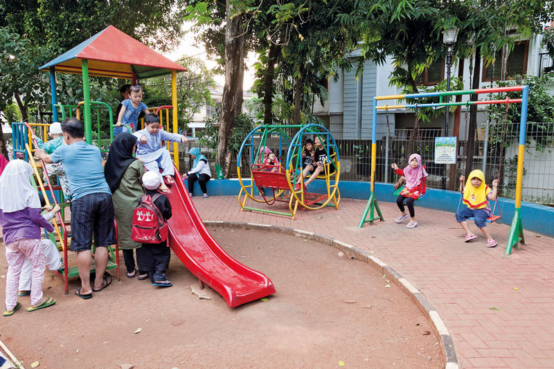 Parents accompanying their children playing in the children playground at Taman Sawo Family Park, South Jakarta